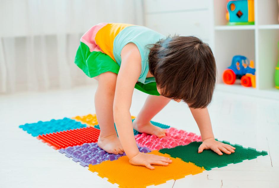 Дитина робить вправи на масажному килимку